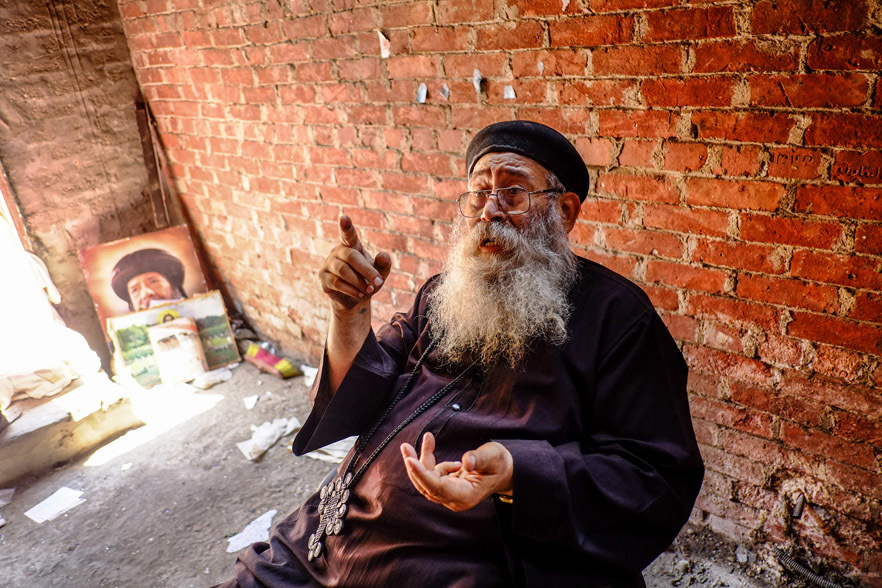 Elderly Coptic priest amongst ruins