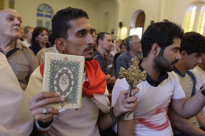 Iraqi holding Cross and Quran in Mar Girgis Church in Baghdad