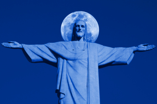 Christ the Redeemer silhouetted against night sky and moon