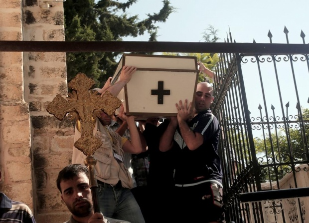 Christians and Muslims help carry Jalila Ayyad's coffin