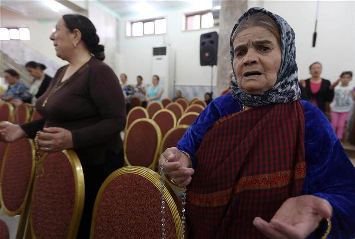 Iraqi Christians who fled the violence in the northern city of Mosul pray at a church in the village of Qaraqosh on July 19