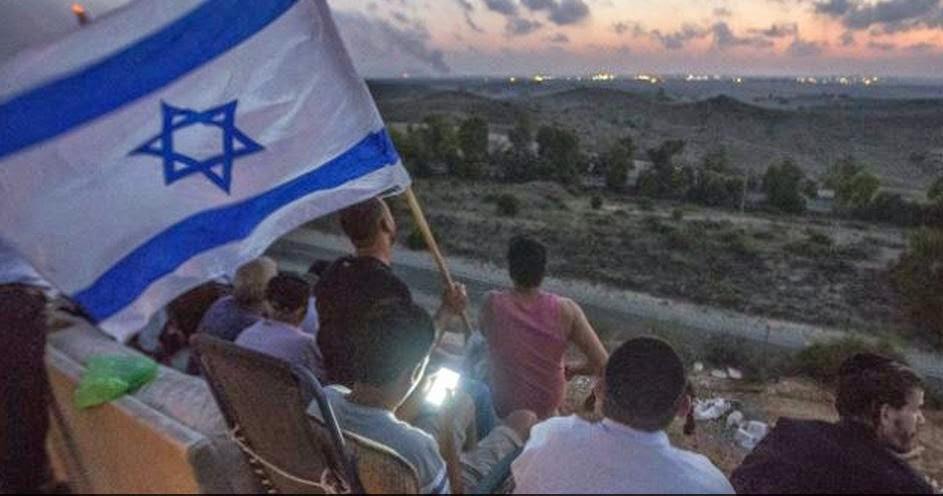 Kippah wearing Israelis enjoying the bombing of Gaza from hill in Sderot