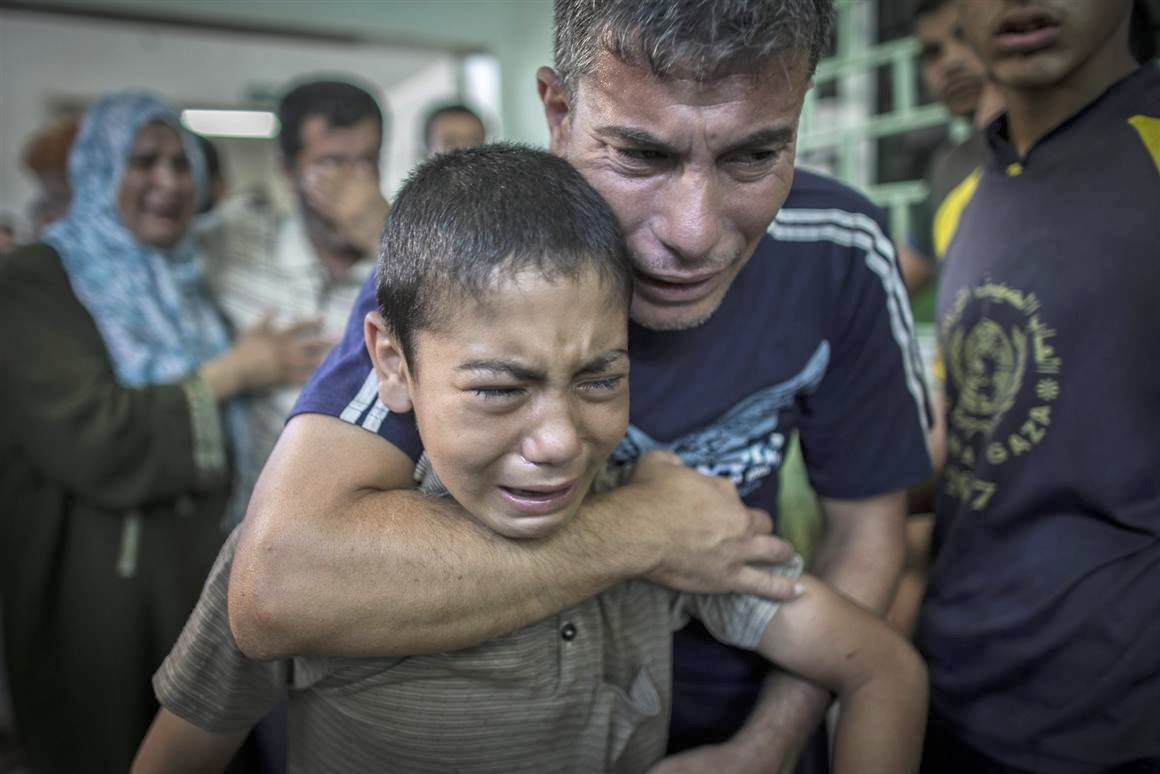 Palestinian father comforts son after loss of relatives in bombing 3_8_14
