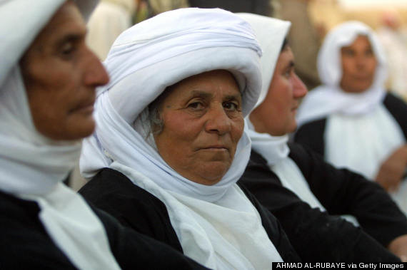 Yezidi women in traditional dress attend